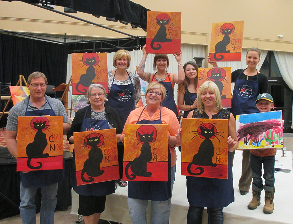 Happy customers show off paintings